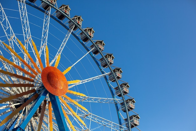Колесо обозрения на фоне голубого неба рядом с rotes rathaus.