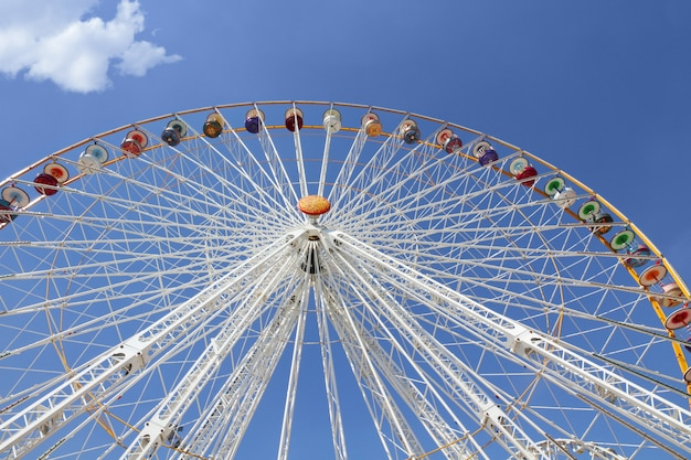 Ferris wheel in an amusement park against blue sky