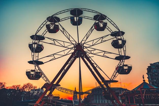 Колесо обозрения на закате. популярный парк аттракционов