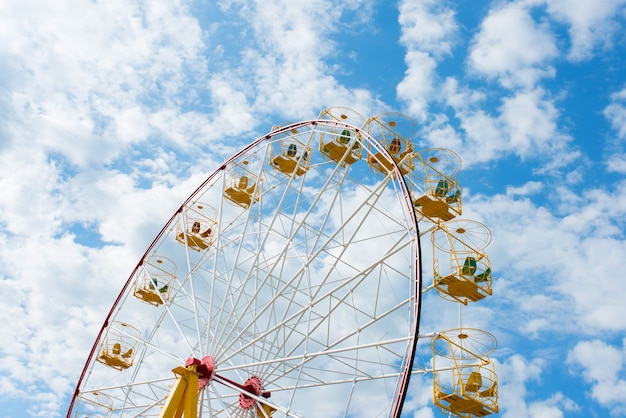 Ferris wheel on a background of blue sky with clouds