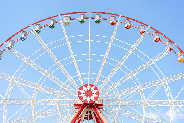 Ferris wheel on a background of bright blue sky