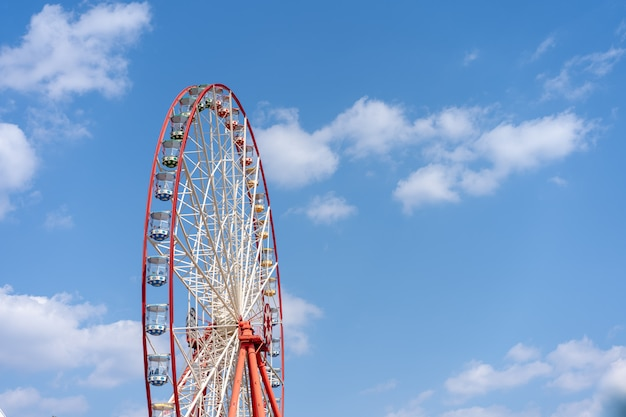 Ferris wheel on a background of bright blue sky