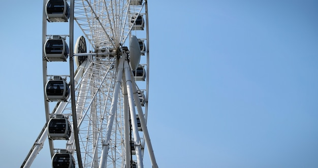 Ferris wheel on a blue sky background in the summer low angle vertical shoot