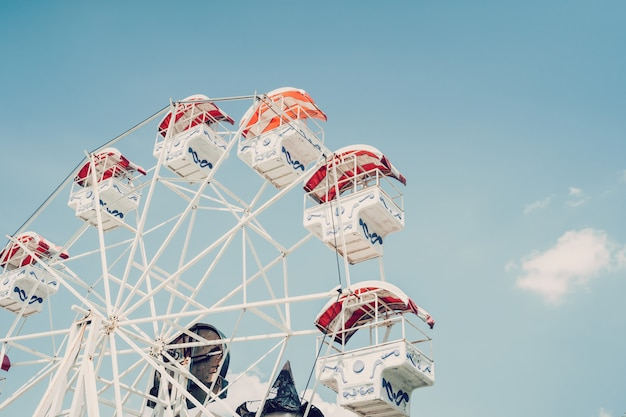 Ferris wheel on cloudy sky background with vintage toned.