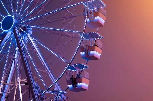 Колесо обозрения с голубой подсветкой на фоне заката. городская сцена. копировать пространство шаблон парка аттракционов