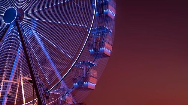 Колесо обозрения с подсветкой на фоне заката. городская сцена. копировать пространство шаблон парка аттракционов