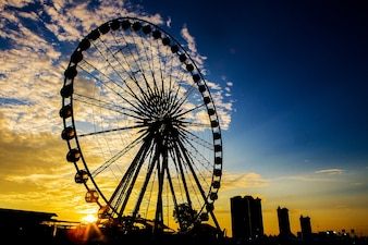Ferris wheel in black silhouette at sunset.