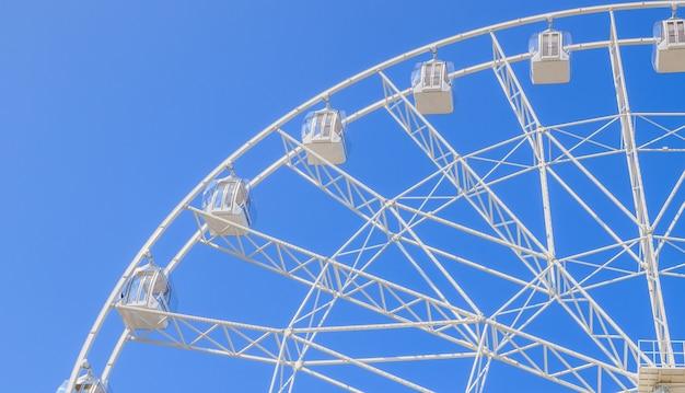 Колесо обозрения в голубом небе. осмотреть город с высоты.