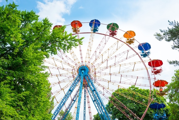 Колесо обозрения в зеленом парке над голубым небом с облаками