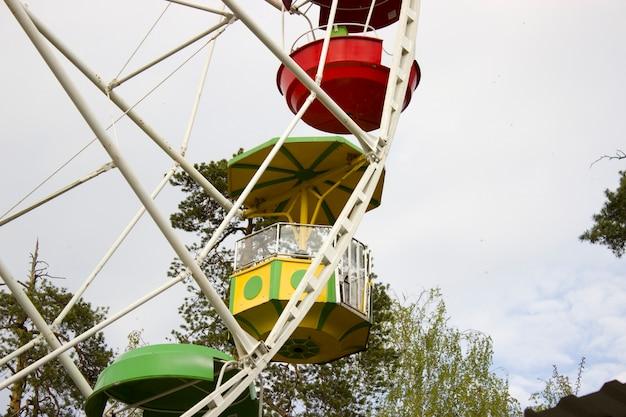 Колесо обозрения в парке против голубого неба
