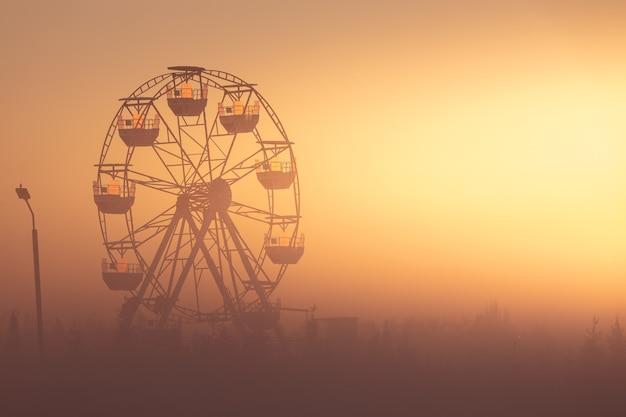 Колесо обозрения в парке на рассвете. прекрасный летний пейзаж. солнечные лучи освещают утренний туман.