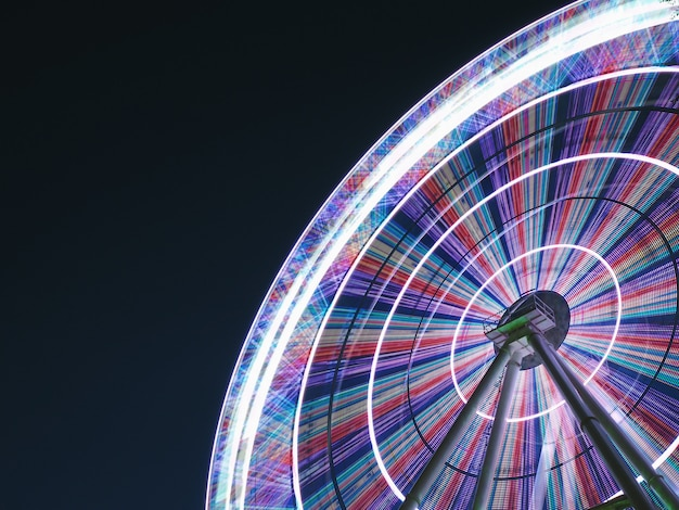 Ferris wheel at night long exposure light lines in a circle on a gradient sky background, copy space