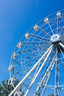 Ferris wheel in a park on a clear blue background.