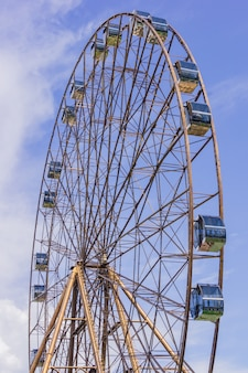 Ferris wheel in sunny summer sochi on blue cloudy sky background