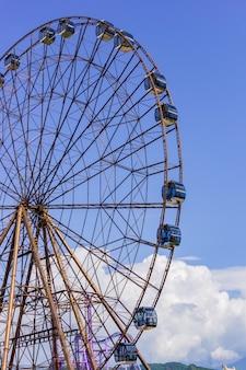 Ferris wheel in sunny summer sochi on blue cloudy sky background
