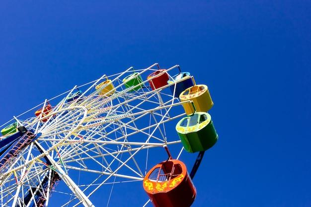 Ferris wheel with colorful cabins at a local fun fair