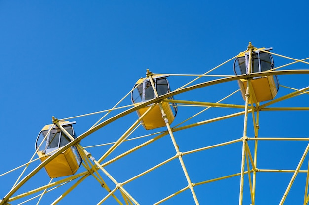 Ferris wheel with yellow cabins. gladness entertainment in city park.