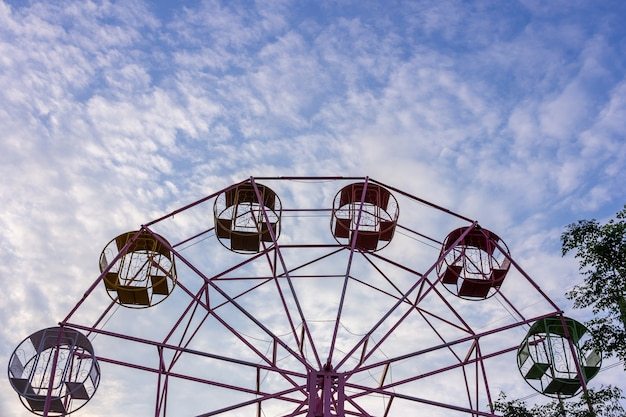 Ferris wheel without people over cloudy sky background