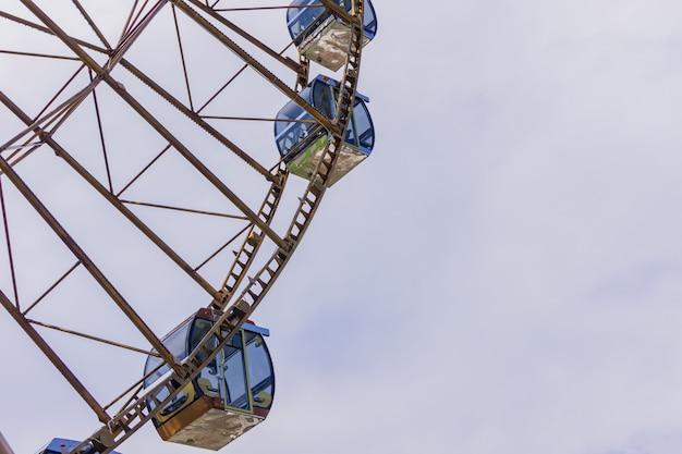 Закройте вверх кабин колеса ferris на предпосылке облачного неба.