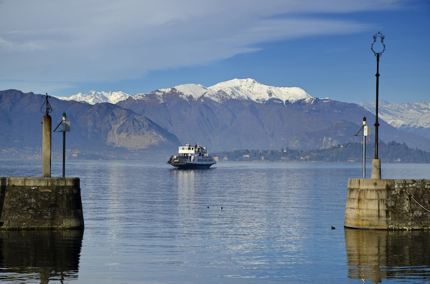 Traghetto su un lago maggiore alpino con montagne innevate in piemonte, italia