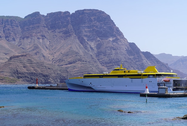 Ferry boat docked in the port next to huge mountain by the sea, landscape of gran canaria. europe,
