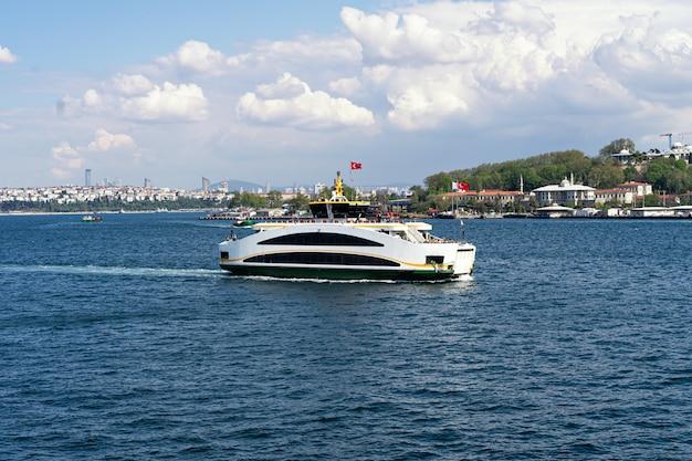 Паром в босфор в стамбуле с видом на город. морские перевозки и пассажирский паром