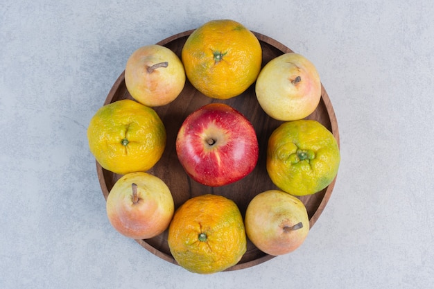 Fersh organic fruits on wooden board. tangerine, red apple and pear.