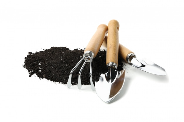 Fertile soil and gardening tools isolated on white isolated