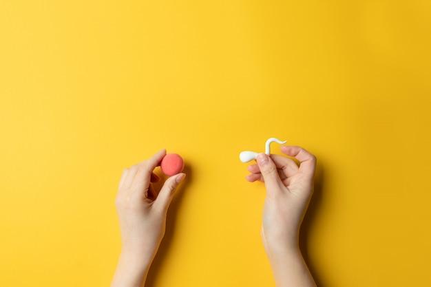 노란색 배경에 여성 계란의 수정. 공간 복사