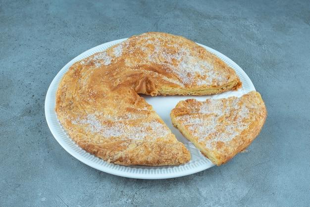 Фесели, азербайджанская слоеная лепешка на блюде, на мраморе.