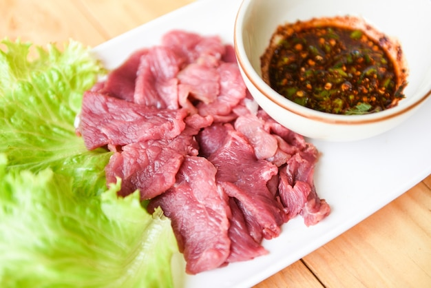 Fesh beef slice on plate with spicy sauce and lettuce