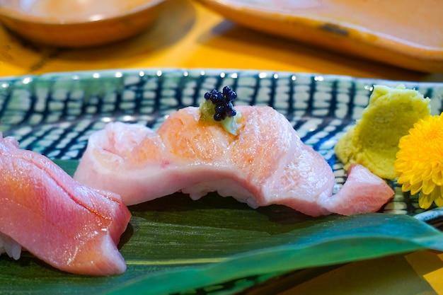 Закройте вверх по отрезанному fesh сырому тунцу или суши otoro или fatty tuna на блюде. японская традиционная еда. выборочный фокус.