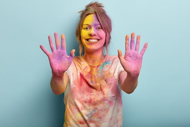 신성하고 재미있는 개념의 축제. 컬러 페인트로 덮여 꽤 쾌활 한 유럽 젊은 여자