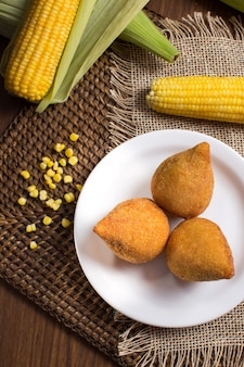 フェスタジュニーナと素朴な背景にトウモロコシとブラジルのコシーニャ