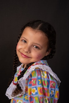Festa junina in brazil, brazilian girl with braids and dressed for junina party doing poses.