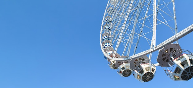 Festival ferris wheel on blue sky background.