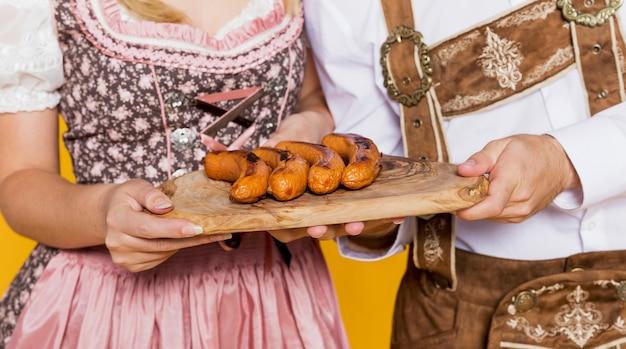 Festival friends holding traditional bratwurst