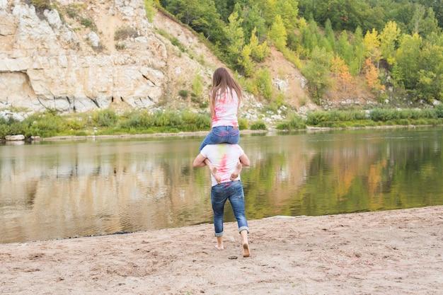 フェスティバルホーリー、夏の観光と自然の概念-自然の上の彼女のボーイフレンドにピギーバックで座っている若い魅力的な女の子。