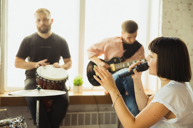 Festival. musician band jamming together in art workplace with instruments. caucasian men and women, musicians, playing and singing together. concept of music, hobby, emotions, art occupation.