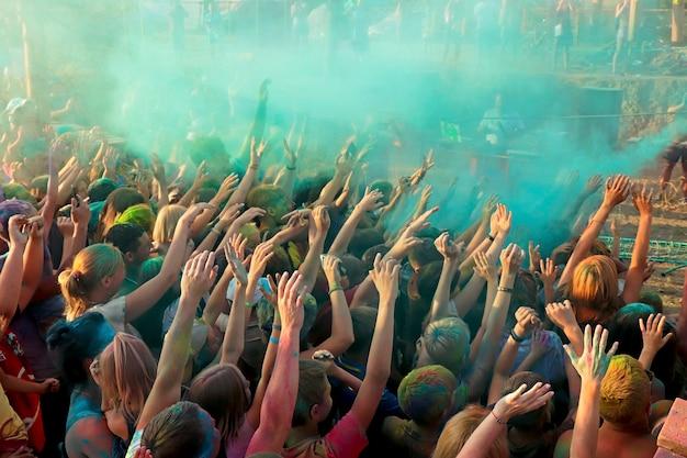 色の祭典色のついた特殊顔料をふりかける人々は、手を上げて、色のついた絵の具をスプレーすることによる新しい感情を待ちます。