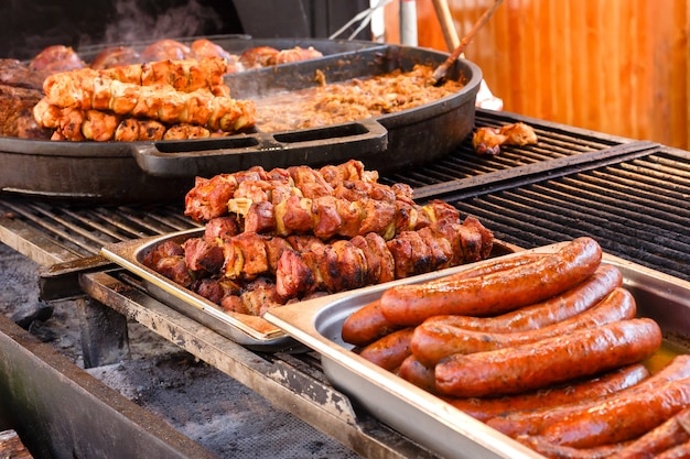 Festival of street food. delicious fresh fried meat and sausages on a pans in a street cafe.