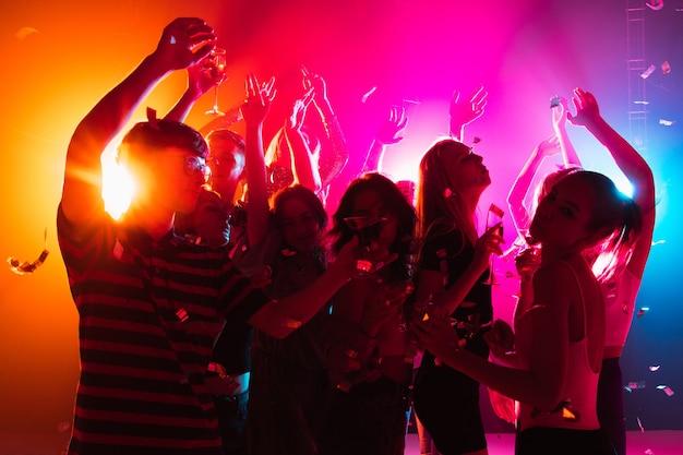 축제. 실루엣의 사람들이 손을 들고 네온 불빛 배경의 댄스플로어에서 춤을 춥니다. 나이트 라이프, 클럽, 음악, 댄스, 모션, 젊음. 밝은 색상과 움직이는 소녀와 소년.