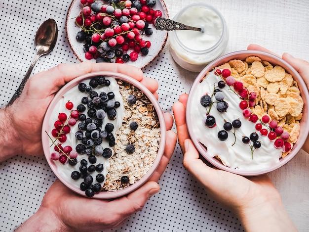 사랑하는 사람들을위한 축제적이고 건강한 아침 식사. 빈티지 그릇, 콘플레이크, 그래 놀라, 요구르트, 신선한 딸기와 젊은 부부의 손.