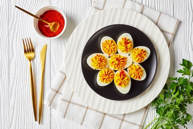 Festive appetizer: devilled eggs with a mix of egg yolks, sriracha sauce, mayonnaise, apple cider vinegar sprinkled with smoked paprika on a plate on a white wooden table, flat lay, close-up