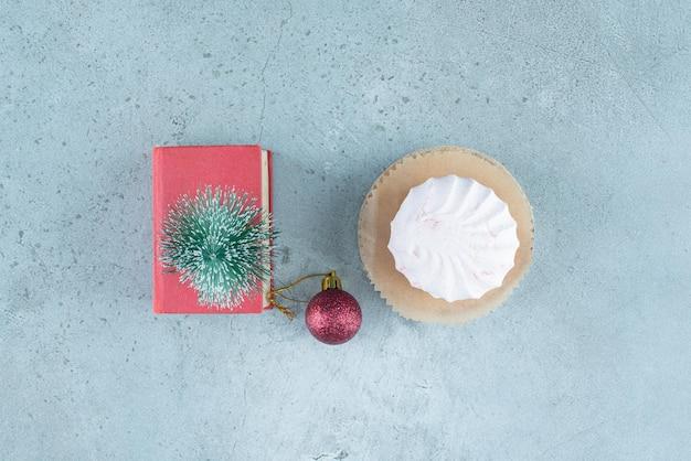 Disposizione festiva di una pallina, una figurina di albero su un piccolo libro e biscotti impilati su marmo.
