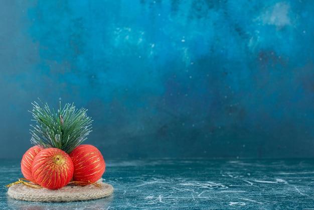 Disposizione festiva di palline e foglie di pino su un sottopentola in marmo.