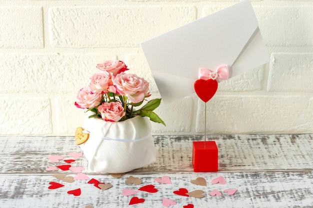 Праздничная композиция из букета розовых роз и конверта с поздравительным письмом к праздникам.