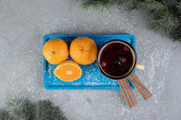 Disposizione festiva con una tazza di metallo e arance sul tavolo di marmo.