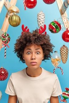 방의 축제 분위기. 곱슬 머리를 가진 깜짝 놀라게 한 어두운 피부를 가진 여자는 도청 된 눈을 쳐다보고 충격적인 뉴스를 듣고 캐주얼 티셔츠를 입고 크리스마스를 위해 집을 장식합니다. 집에서 즐거운 휴일 시간.