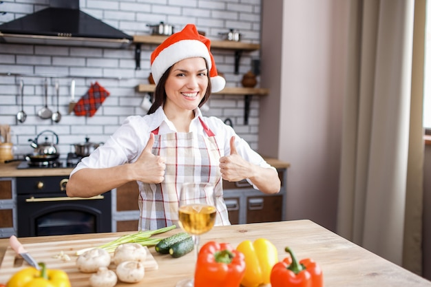Festive attractive adult woman hold both big thumbs up and smile.